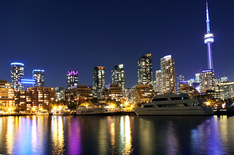 Toronto night skyline with luxury yachts of the Ultra Rich in front of their Luxury Condos