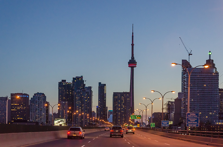 Toronto skyling including new condo projects as seen from highway at night with cars